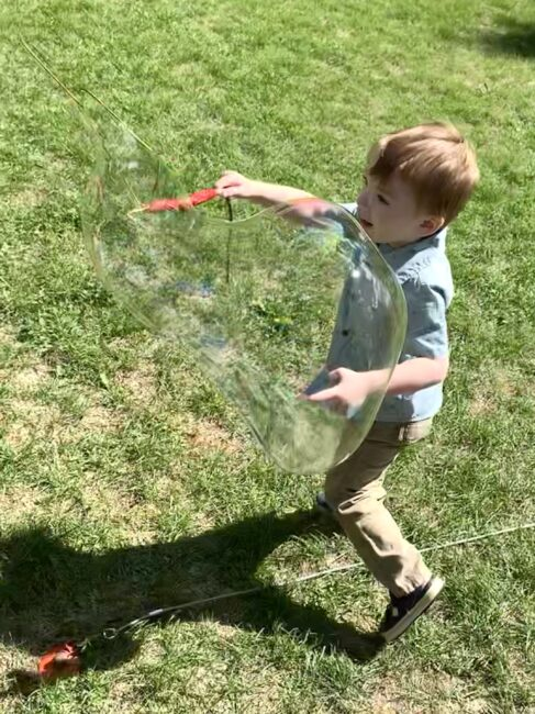 Your kids will love making bubbles with these DIY giant bubble wands! Use supplies from around the house and have lots of gross motor fun.