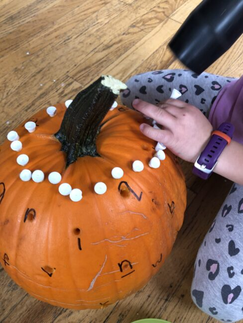 Making a circle pattern on a pumpkin after the activity.