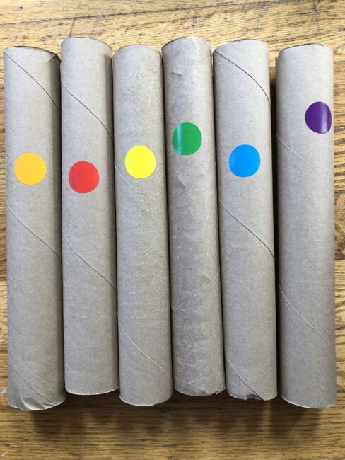 Preparing paper rolls for balancing colored balls on top.
