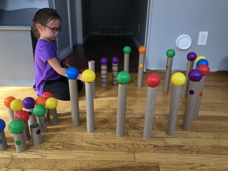 Making a fort with ball pit balls and paper rolls for fine motor fun.
