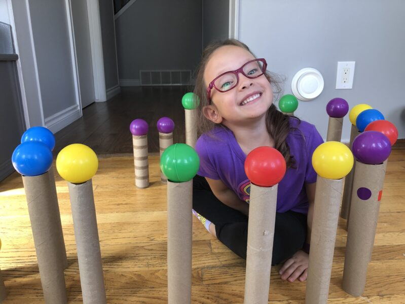Balancing ball pit balls on paper towel rolls to make a for to sit in for kids.