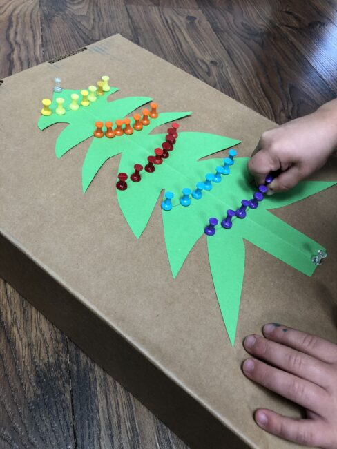 Use push pins to decorate a Christmas tree for fine motor skills and color sorting or patterns with this simple activity.