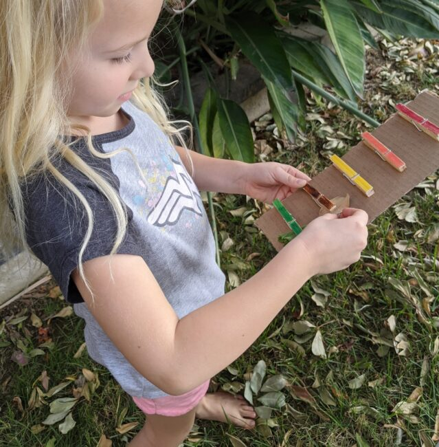 A simple and fun nature color scavenger hunt with clothespins activity for outdoor exploring, fine motor skills, and color learning for kids.