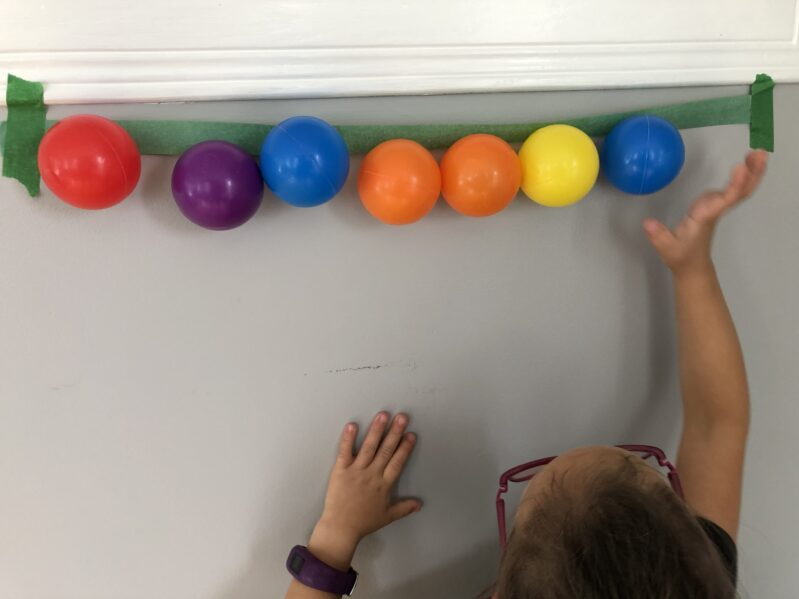 Reach up and stick balls to a line of painters tape for gross motor fun at home.