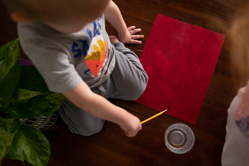 Toddler paint with water to create construction paper art and sensory play activity.