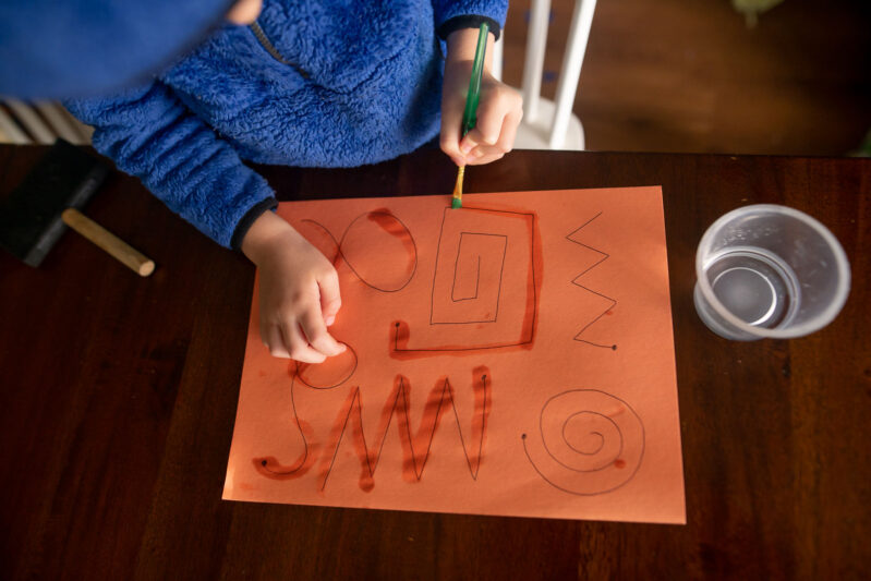 Paint with water tracing on construction paper activity for kids.