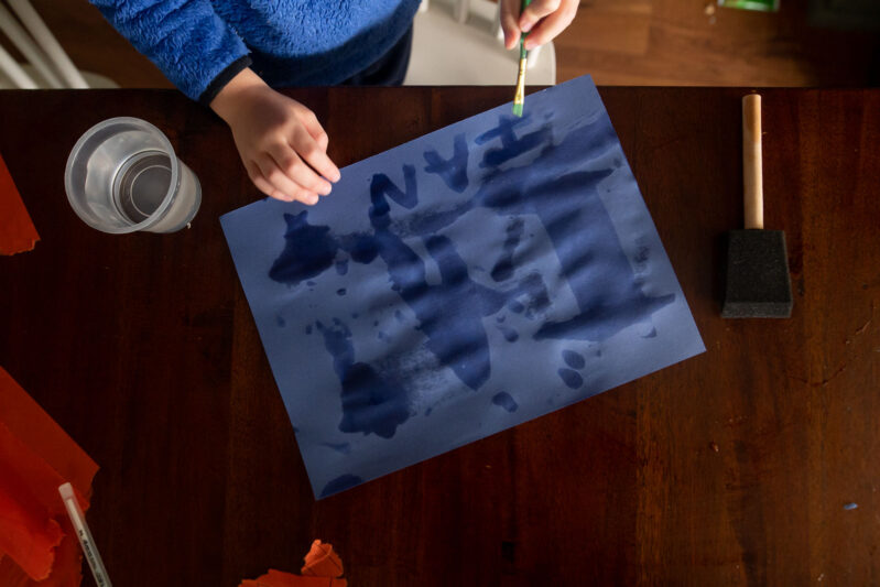 Writing and painting with water on construction paper