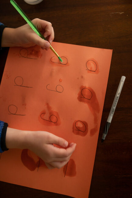 Tracing letters paint with water on construction paper.