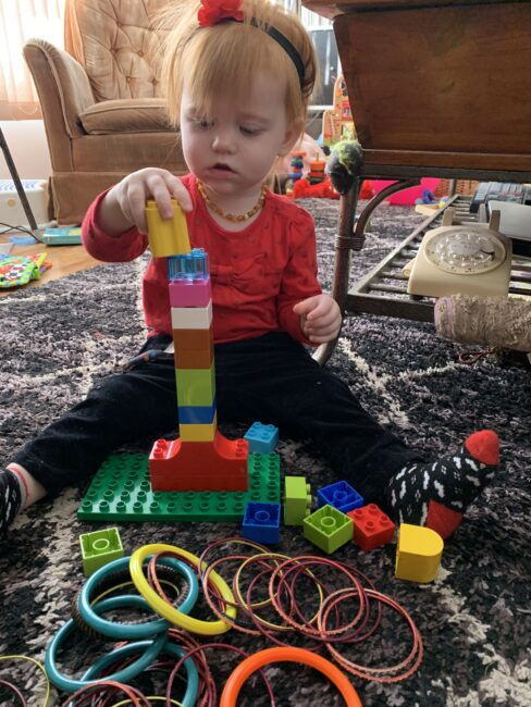 Super simple DIY ring stacking fine motor activities for toddlers using Lego blocks and bracelets.
