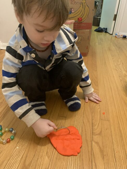 Sensory and fine motor play cutting playdough with shower curtain rings.