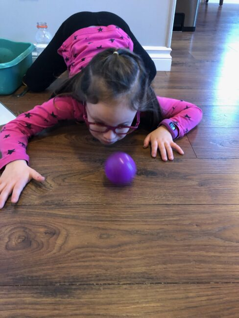 Blowing the ball across the room.