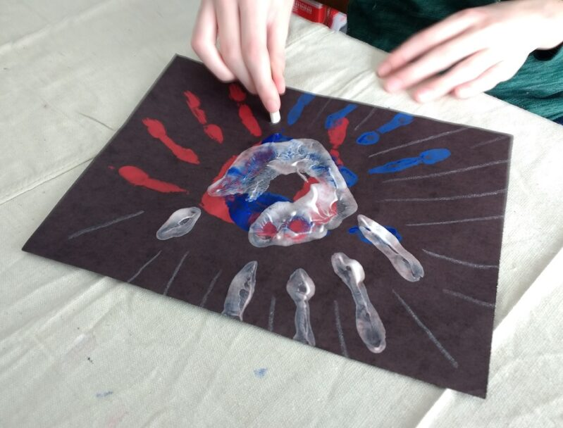 Adding lines to finish the 4th of July handprint preschool craft.