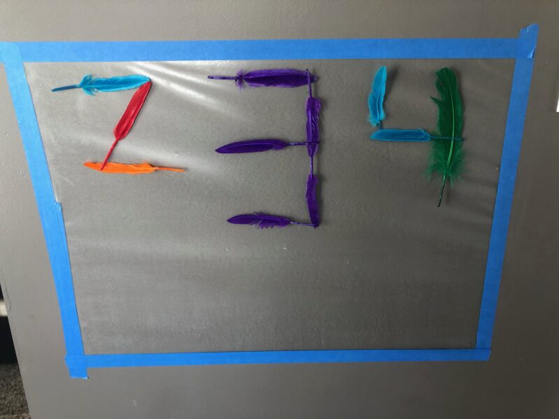 Numbers activity or just sensory play with feather and contact paper on the wall.