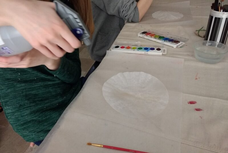 Spraying coffee filter with water for an autumn craft
