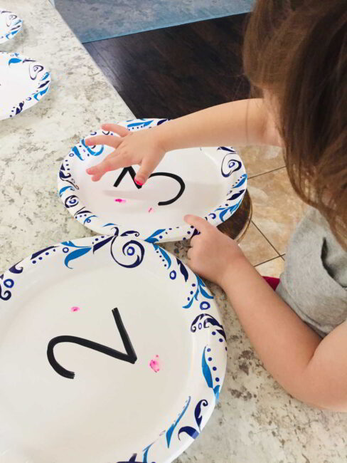 Count on your hands and also with finger paints dabbing to match the number.
