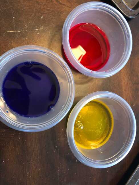 Water and food coloring or watercolors for fine motor color mixing activity.