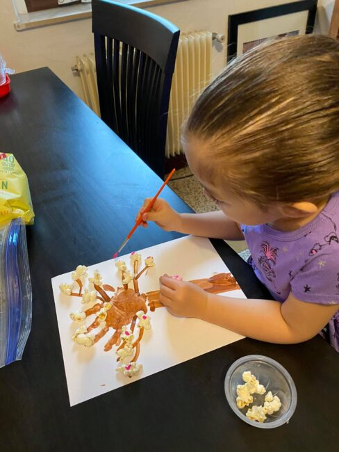Add dots of pink paint to popcorn to create a cherry blossom spring tree craft with your kids.
