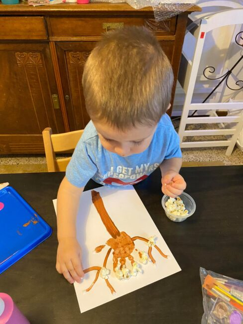 Glue popcorn to a handprint to make a cherry blossom spring tree craft for toddlers and preschoolers.