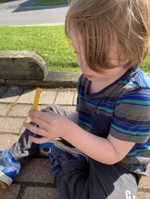 Trying to balance the stick as it on his finger.