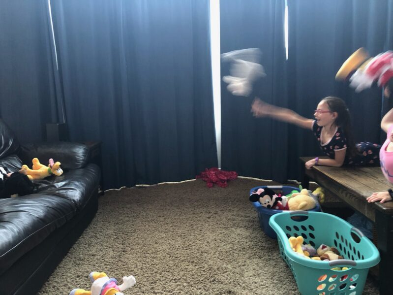 Toss a stuffed animal to a target, such as the couch while lying town on your tummy.