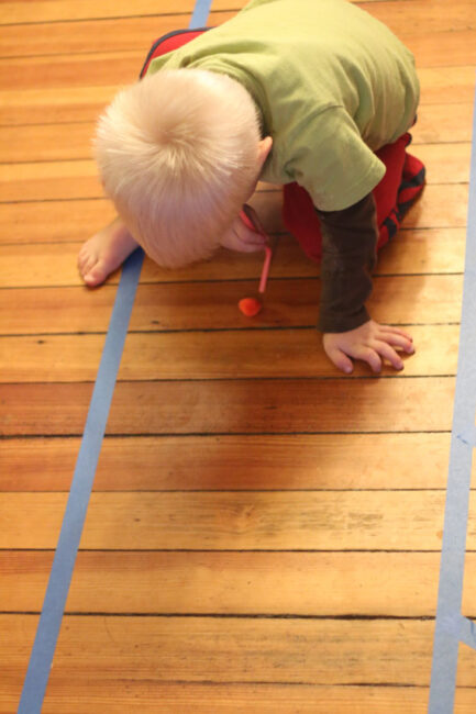 Improve fine motor skills while playing a fun gross motor game with this easy pom pom race of blowing with straws around the floor at home.