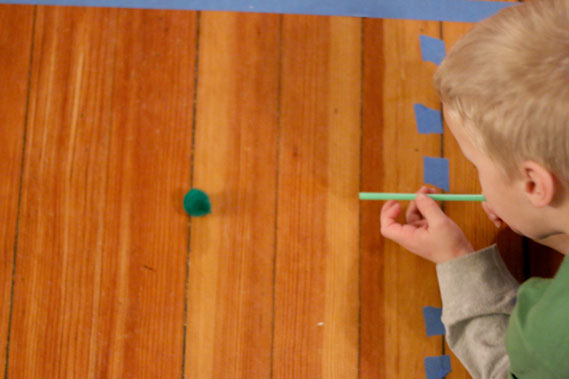 Set up a quick racetrack on the floor and create a fun and easy blowing with straws and pom poms race for your toddlers and preschoolers to improve fine and gross motor skills.