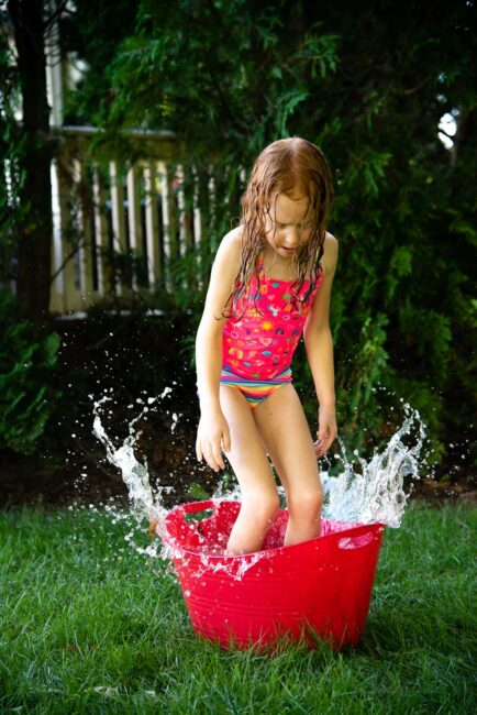 Beat the heat this summer with a simple fun DIY backyard water obstacle course using household supplies for your kids to cool down outside.