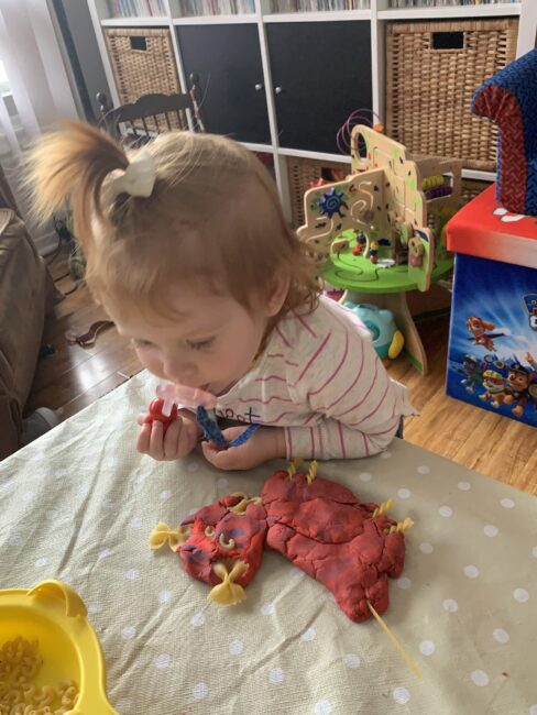 My toddler admiring the complete family portraits made with play dough and pasta!