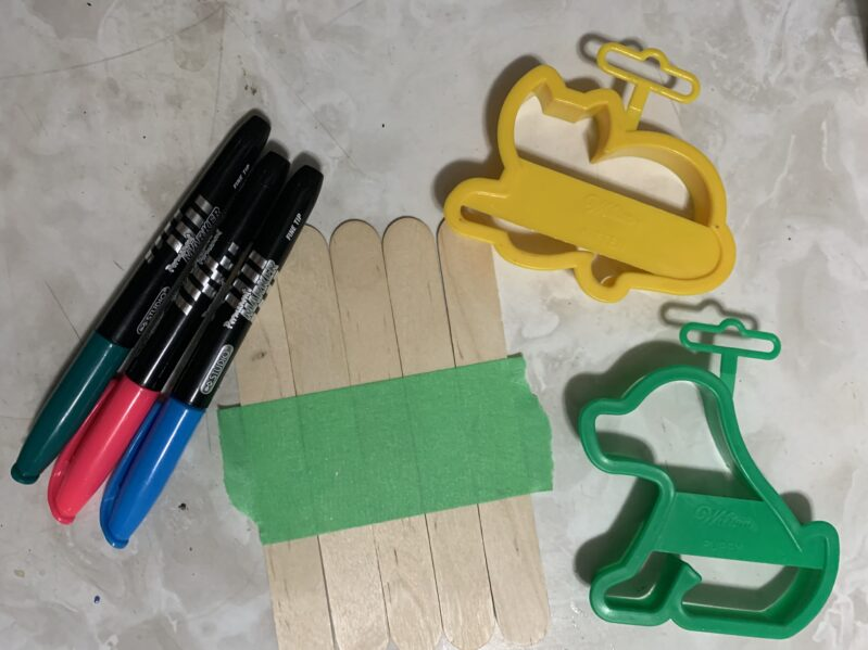 Line up the craft sticks and tape them together so they don't slip while you trace your shape