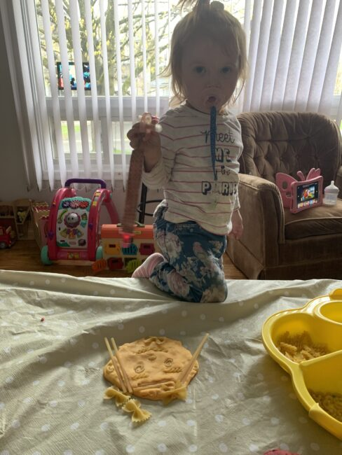 My toddler making her self portrait using play dough and pasta