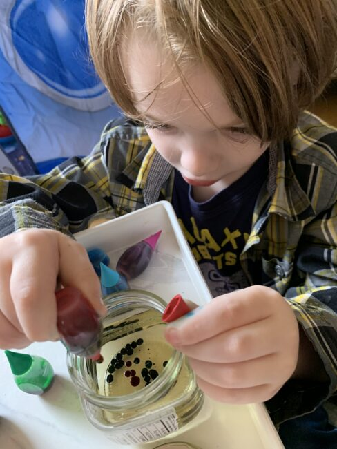 Fine motor practice squeezing food coloring drops into small jars of oil.