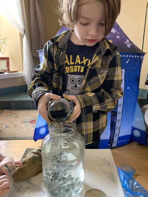 Pour the mixed up food coloring and oil into large jar of water.