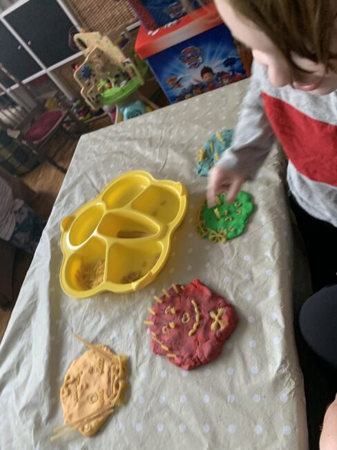 Making family portraits with play dough and pasta!