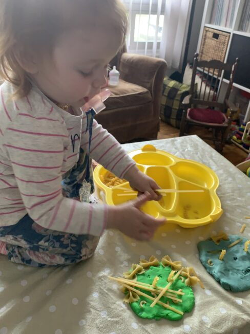 My two year old adding lots and lots of hair to her play dough face of mommy.
