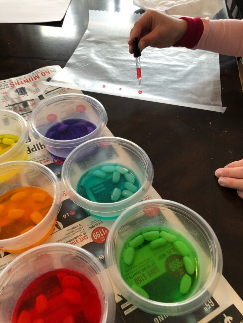 drop painting with jelly bean colored water onto wax paper