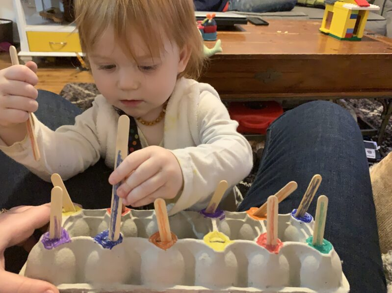 Showing Mommy she knows where the blue peg is supposed to go.